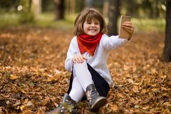 Portrait of funny little girl grimacing while taking selfie over autumn stock image