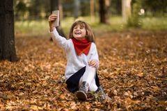 Portrait of funny little girl grimacing while taking selfie over autumn stock photo