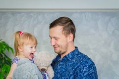 Portrait of funny little girl and her father at home stock photography