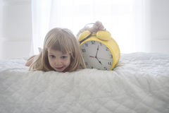 Portrait of funny little girl with huge alarm clock over white background Stock Photos