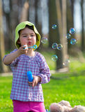 Portrait of funny lovely little girl blowing soap bubbles in the park Stock Images