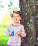 Portrait of funny lovely little girl blowing soap bubbles in the park Royalty Free Stock Photography