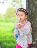 Portrait of funny lovely little girl blowing soap bubbles in the park Royalty Free Stock Photos