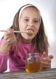 Portrait of funny lovely little girl eat honey. Close up Stock Images