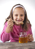 Portrait of funny lovely little girl eat honey. Close up Royalty Free Stock Images