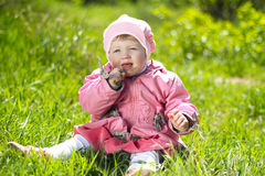 Portrait of funny lovely little girl sitting on a green grass Royalty Free Stock Images