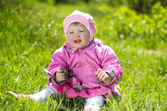 Portrait of funny lovely little girl sitting on a green grass Royalty Free Stock Photography