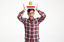 Portrait a funny male student holding books. With green apple on his head and screaming isolated over white background Stock Images