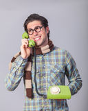 Portrait of funny man in glasses. With telephone on a gray background Royalty Free Stock Image