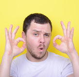 Portrait of funny man showing OK gesture with hands against yell. This image is made in studio with model standing against colored backgrounds.Set of various Stock Images