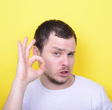 Portrait of funny man showing OK gesture with hands against yell. This image is made in studio with model standing against colored backgrounds.Set of various Royalty Free Stock Images