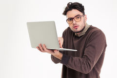 Portrait of a funny man using laptop compter. And looking at camera isolated on a white background Stock Photography