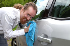 Portrait of funny man washing car. With a cloth Royalty Free Stock Images