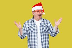 Portrait of funny modern middle aged man in red cap, eyeglasses. And checkered shirt standing with hands up and surprised face looking at camera. Indoor, studio royalty free stock photo