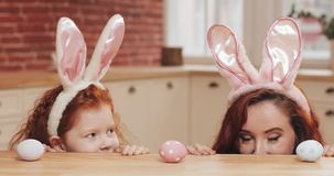 Portrait of funny mom and her daughter wearing bunny ear with easter eggs looking into the camera. happy family having