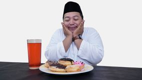 Portrait of overweight muslim man with head cap or songkok pray before eat and drink for islam break fasting