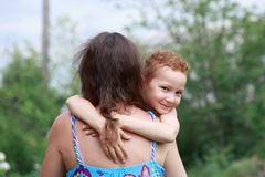 Portrait of funny redhead boy with freckles hugs his mom around the neck royalty free stock images