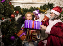 Portrait of funny Santa Claus at home with. Christmass tree, real normal men and snowmaiden in blue, bringing gifts Stock Photos