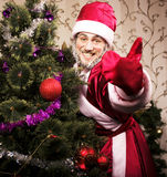 Portrait of funny Santa Claus at home with christmass tree. Thumbs up Royalty Free Stock Photography