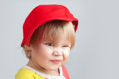 Portrait of funny smiling baby girl in red baseball cap. Studio portrait of funny smiling baby girl in red baseball cap over gray wall background Royalty Free Stock Images