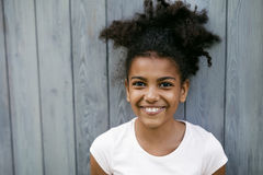 Portrait of a funny smiling girl. Standing at wall outdoors Royalty Free Stock Images