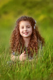Portrait of Funny smiling little girl with curly hair in green g Stock Images