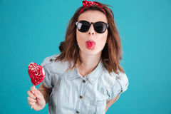 Portrait of a funny stylish girl in sunglasses showing tongue Royalty Free Stock Photos