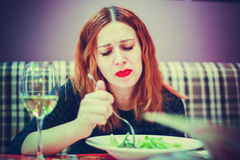 Portrait of funny woman plays the fool eats salad in cafe Stock Photography