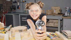 Portrait of funny 10 year old girl in wood carpentry holding an electronic drill, posing at camera. Little builder. Concept stock video footage