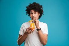 Portrait of a funny young african man. Drinking tropical cocktail isolated over blue background Stock Photo