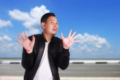 Asian Man with Hands Up Surrender. Portrait of funny young Asian man wearing black leather jacket shows hands up surrender gesture, over cloudy blue sky Stock Photography