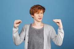 Portrait of funny young attractive guy with ginger hair in casual clothes making faces with hands, talking to them with Stock Images