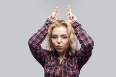 Portrait of funny young beautiful young woman in casual red checkered shirt standing with horns gesture hands on head and looking stock images