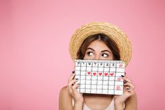 Portrait of a funny young girl. In summer hat hiding behind a periods calendar and looking away at copy space isolated over pink background Stock Images