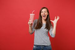 Portrait of funny young woman blinking, keeping mouth wide open, holding plastic cup of cola or soda isolated on bright. Red background. People sincere emotions royalty free stock photos