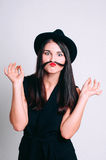 Portrait of funny young woman with a fake mustache. Portrait of funny young woman in a hat holding her hair like a fake mustache, on white background royalty free stock photo
