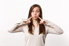 Portrait of funny young woman in light clothes pointing index fingers on blowing cheeks isolated on white wall. Background in studio. People sincere emotions royalty free stock images
