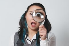 Portrait of a funny young woman looking at the camera through magnifying glass on gray background royalty free stock photography