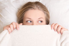 Portrait of funny young woman lying in bed under blanket Royalty Free Stock Image