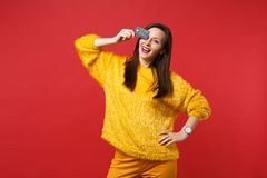 Portrait of funny young woman in yellow fur sweater covering eye with credit bank card isolated on bright red wall. Background in studio. People sincere royalty free stock images