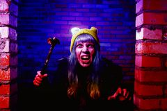 Portrait of funny zombie girl in halloween time with hammer Stock Photography