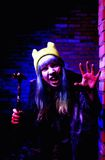 Portrait of funny zombie girl in halloween time with hammer Stock Photo