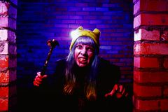 Portrait of funny zombie girl in halloween time with hammer Stock Images