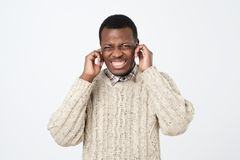 Furious afroamerican man covering his ears. I am tired of this terrible rattle and sounds concept. Portrait of furious afroamerican man covering his ears. I am royalty free stock image