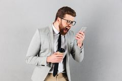 Portrait of a furious businessman dressed in suit. And eyeglasses yelling at mobile phone while standing and holding coffee cup  over gray background Royalty Free Stock Photo