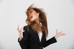 Portrait of a furious businesswoman dressed in suit screaming. Isolated over gray background Royalty Free Stock Images