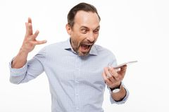 Portrait of a furious mature man dressed in shirt yelling. At mobile phone isolated over white background Royalty Free Stock Photo