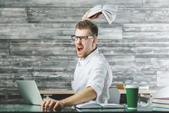 Furious male at workplace. Portrait of furious young european male thowing stuff at workplace. Stress, problem concept royalty free stock photos