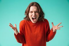 Portrait of a furious young woman dressed in sweater. Screaming isolated over blue background Stock Images