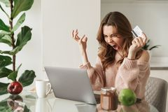 Portrait of a furious young woman holding credit card royalty free stock image